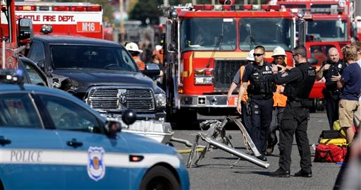 """Emergency personnel work at the scene of a fatal collision involving a charter bus, background, and a """"Ride the Ducks"""" amphibious tour bus, right, on the Aurora Bridge in Seattle on Thursday, Sept. 24, 2015. (AP Photo/Elaine Thompson)"""