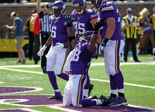 Minnesota Vikings running back Adrian Peterson (28) celebrates a touchdown against the San Diego Chargers with, from left to right, quarterback Teddy Bridgewater (5), tight end Rhett Ellison (85) and tackle Matt Kalil (75) in the first half of an NFL foot