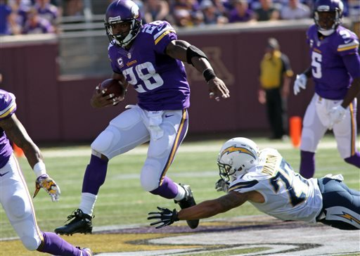 Minnesota Vikings running back Adrian Peterson (28) breaks away from San Diego Chargers strong safety Jimmy Wilson (27) in the first half of an NFL football game in Minneapolis, Sunday, Sept. 27, 2015. (AP Photo/Andy Clayton-King)
