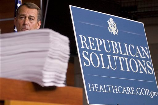 In this Oct. 29, 2009 file photo then-House Minority Leader John Boehner of Ohio stands behind a copy of the Democrat's version of the health care bill during a news conference on Capitol Hill in Washington. Boehner's announced exit as House speaker and