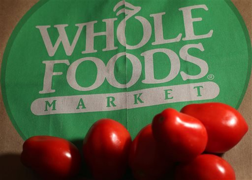In this Monday, July 29, 2013, file photo, produce is placed on a Whole Foods paper bag in Andover, Mass. Grocery chain Whole Foods is cutting about 1,500 jobs, or 1.6 percent of its workforce, over the next eight weeks as it looks to lower prices and kee