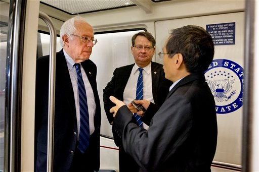 Democratic presidential candidate Sen. Bernie Sanders, I-Vt., left, is interviewed as he leaves after a Senate vote on Capitol Hill in Washington, Wednesday, Sept. 30, 2015. to approved a stopgap spending bill to avert a government shutdown. Sen. Gary Pet