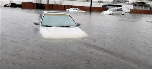 """Several cars are submerged floodwaters thoughout Georgetown, S.C., on Sunday, Oct. 4, 2015. The rainstorm drenching the East Coast brought more misery Sunday to South Carolina, cutting power to thousands, forcing hundreds of water rescues and closing """"too"""