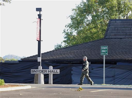 A Douglas County Sheriff's deputy walks past Snyder Hall at Umpqua Community College, Sunday, Oct. 4, 2015, in Roseburg, Ore. Armed with multiple guns, suspect Chris Harper-Mercer walked into a class at Snyder Hall on Thursday, killing nine and wounding s