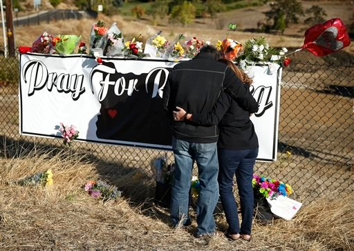 Charley Thompson, left, and his wife Rachel Thompson embrace as they place flowers at a makeshift memorial near the road leading to Umpqua Community College, Saturday, Oct. 3, 2015, in Roseburg, Ore. Armed with multiple guns, Chris Harper Mercer walked in