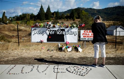 A woman visits a makeshift memorial near the road leading to Umpqua Community College, Saturday, Oct. 3, 2015, in Roseburg, Ore. Armed with multiple guns, Chris Harper Mercer walked in a classroom at the community college, Thursday, and opened fire, killi