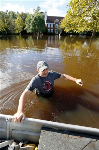 Ethan Abbott pulls his boat down Mayfield St. to help a friend get personal items out of a flooded house in the Ashborough subdivision near Summerville, S.C., Tuesday, Oct. 6, 2015. Residents are concerned that the Ashley river will continue to rise as fl