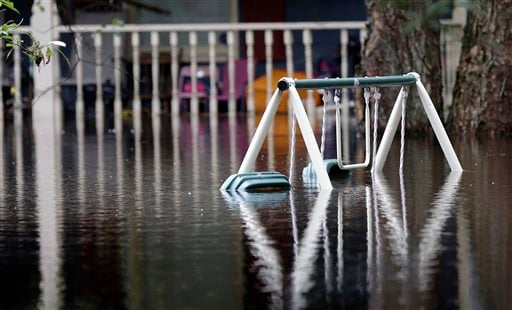 A swing set is nearly covered in floodwater on Roundtree Road along the Lynches River in Effingham, S.C., Tuesday, Oct. 6, 2015. The Carolinas saw sunshine Tuesday after days of inundation, but it could take weeks to recover from being pummeled by a histo
