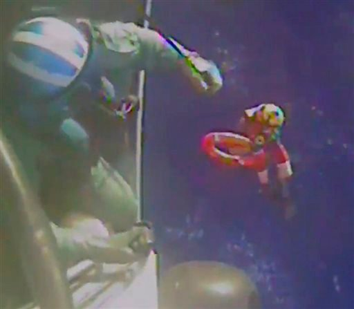 In this Sunday, Oct. 4, 2015 photo made from video and released by the U.S. Coast Guard, a Coast Guard crew member is moved back to the helicopter after investigating a life boat, that was found from the missing ship El Faro. On Monday, four days after th