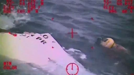In this Sunday, Oct. 4, 2015 photo made from video and released by the U.S. Coast Guard, a Coast Guard crew member investigates a life boat, that was found from the missing ship El Faro. On Monday, four days after the ship vanished, the Coast Guard conclu