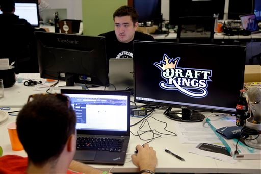 In this Sept. 9, 2015, file photo, Len Don Diego, marketing manager for content at DraftKings, a daily fantasy sports company, works at his station at the company's offices in Boston.