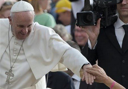 A faithful touches Pope Francis' hand as he is driven through the crowd during his weekly general audience in St. Peter's Square at the Vatican, Wednesday, Oct. 7, 2015. (AP Photo/Alessandra Tarantino)