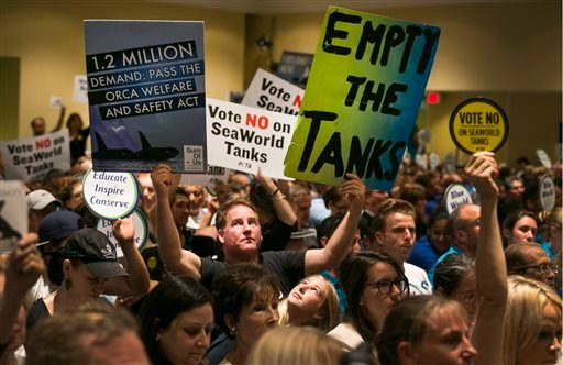 Animal rights activist Kirby Kotler, with his daughter Kirra, 12, from Malibu, Calif., holds up signs as opponents and supporters fill the room during a California Coastal Commission meeting, Thursday, Oct. 8, 2015, in Long Beach, Calif.