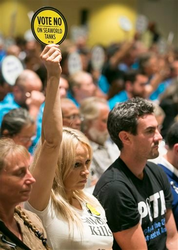 "Animal rights activist and actress Pamela Anderson, left, raises a sign reading ""Vote No, on SeaWorld Tanks, PETA"" as opponents and supporters fill the room during a California Coastal Commission meeting, Thursday, Oct. 8, 2015, in Long Beach, Calif."