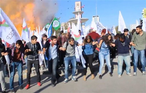 In this image made from video, participants in a peace rally react as an explosion happens behind them, in Ankara, Saturday, Oct. 10, 2015. Two explosions on Saturday targeted a peace rally by opposition supporters and Kurdish activists in Ankara, killing