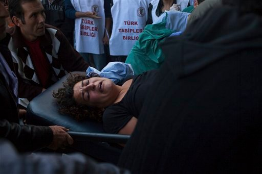 People wheel a wounded woman at the site of an explosion in Ankara, Turkey, Saturday, Oct. 10, 2015. Two bomb explosions targeted a peace rally, organised by the country's public sector workers' trade union, in the Turkish capital killing dozens of people