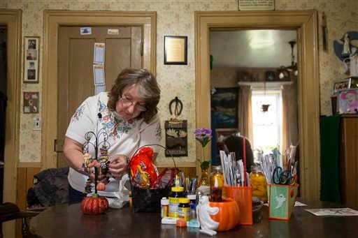 In this Friday, Oct. 9, 2015, photo, Carol Mead decorates her home for Halloween, in Montrose, Pa. Mead, 67, is retired and her husband, 70, must work at a local rock quarry to close the gap from her Social Security. (AP Photo/Brett Carlsen)