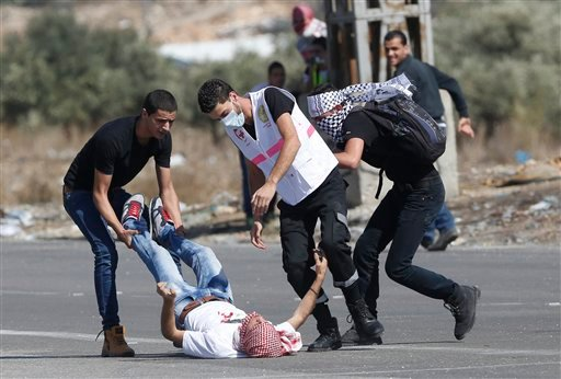 An injured Palestinian demonstrator is helped during clashes at the Hawara checkpoint near of the West Bank city of Nablus, Sunday, Oct. 11, 2015. Tensions in he West Bank continued with near-daily violent demonstrations. At least 45 Palestinians were wou