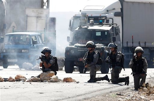 Israeli border policemen takes positions during clashes with Palestinians at the Hawara checkpoint near of the West Bank city of Nablus, Sunday, Oct. 11, 2015. Tensions in he West Bank continued with near-daily violent demonstrations. At least 45 Palestin