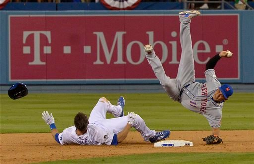 New York Mets shortstop Ruben Tejada falls after a slide by Los Angeles Dodgers' Chase Utley during the seventh inning of an NL Division Series baseball game Saturday, Oct. 10, 2015, in Los Angeles.