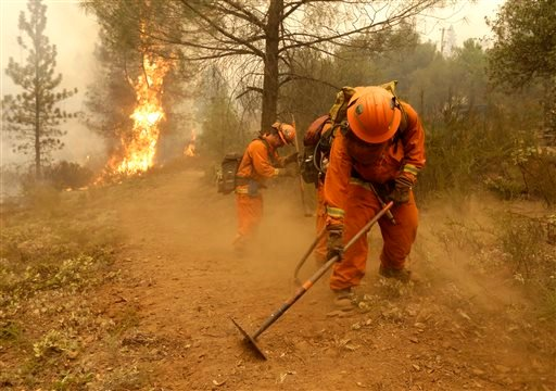 In this Sept. 12, 2015, file photo, a California Department of Corrections and Rehabilitation inmate work crew builds a containment line ahead of flames from a fire near Sheep Ranch, Calif.