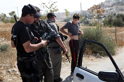 Israeli border police search a man driving out of the Palestinian neighborhood of Jabal Mukaber in Jerusalem, Wednesday, Oct. 14, 2015. Israel erected checkpoints and deployed several hundred soldiers in the Palestinian areas of the city Wednesday as it s