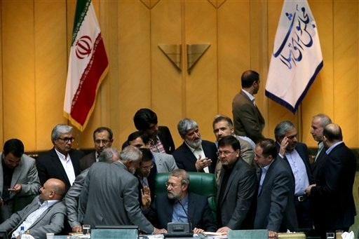 In this photo taken on Sunday, Oct. 11, 2015, Iran's parliament speaker Ali Larijani, center, speaks with lawmakers in an open session of parliament while discussing a bill on Iran's nuclear deal with world powers, in Tehran, Iran. Iran's parliament voted