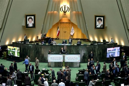 In this photo taken on Sunday, Oct. 11, 2015, head of Iran's Atomic Energy Organization Ali Akbar Salehi, center, ends his speech in an open session of parliament while discussing a bill on Iran's nuclear deal with world powers, in Tehran, Iran. Iran's pa