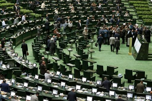 In this photo taken on Sunday, Oct. 11, 2015, lawmakers get up from their seats to talks to head of Iran's Atomic Energy Organization Ali Akbar Salehi after his speech in an open session to discuss a bill on Iran's nuclear deal with world powers, at the p