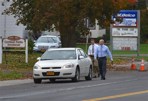 Investigators with the New York State Police walk down Oneida Street after speaking with residents as part of their investigation following the death of their 19-year-old Lucas Leonard, Tuesday, Oct. 13, 2015 in Chadwicks, N.Y.