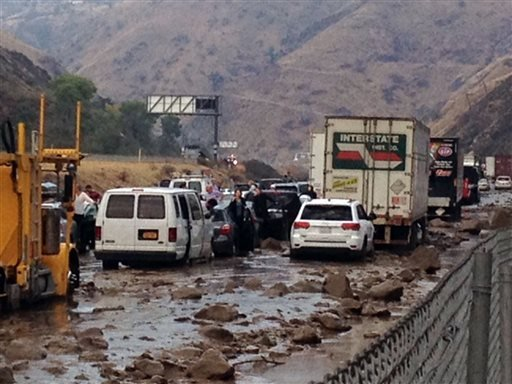 In this photo provided by Caltrans, vehicles are stopped in mud on California's Interstate-5 after flooding Thursday, Oct. 15, 2015. (Caltrans via AP)