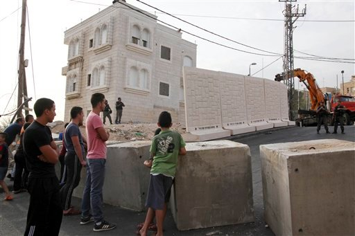 Palestinians watch a wall being built between Palestinian and Jewish neighborhoods in Jerusalem Sunday, Oct. 18, 2015. Palestinians in Jerusalem, more than one-third of the city's population, have awoken to a new reality: Israeli troops are encircling Ara
