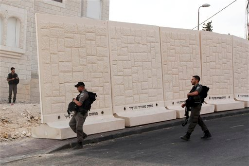 Israeli border policemen walk by the wall being built between Palestinian and Jewish neighborhoods in Jerusalem Sunday, Oct. 18, 2015. Palestinians in Jerusalem, more than one-third of the city's population, have awoken to a new reality: Israeli troops ar