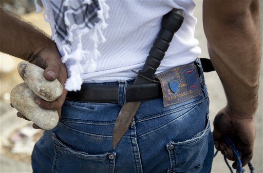A Palestinian demonstrator has a knife in his belt and rocks in his hand during clashes with Israeli troops, near Ramallah, West Bank, Sunday, Oct. 18, 2015. (AP Photo/Majdi Mohammed)