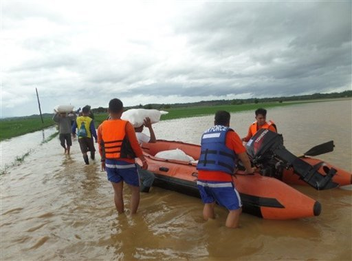 This photo provided by the Philippine Air Force, Philippine Air Force rescue team use rubber boats to distribute relief goods in Isabela province, northern Philippines on Sunday Oct. 18, 2015. Slow-moving Typhoon Koppu weakened after blowing ashore with f