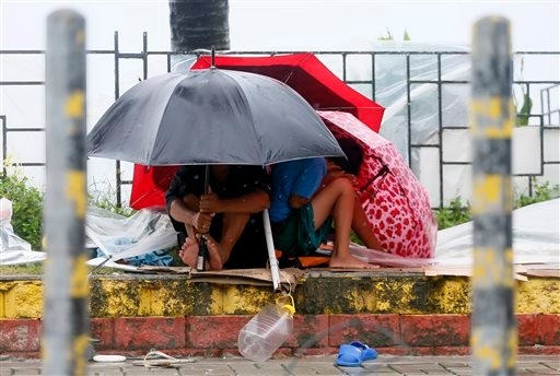 Residents huddle together under their umbrellas as strong winds and slight rain are brought by Typhoon Koppu Sunday, Oct. 18, 2015 in Manila, Philippines. The slow-moving typhoon blew ashore with fierce wind in the northeastern Philippines early Sunday, t