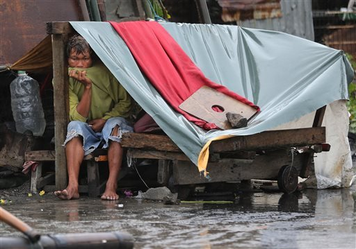 A Filipino man sits inside his makeshift home as strong winds and rains caused by Typhoon Koppu hits the coastal town of Navotas, north of Manila, Philippines on Sunday, Oct. 18, 2015. Slow-moving Typhoon Koppu blew ashore with fierce wind in the northeas