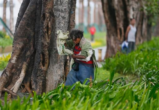 A woman seeks shelter behind a tree as strong winds and slight rain brought by Typhoon Koppu hit Manila, Philippines Sunday, Oct. 18, 2015. The slow-moving typhoon blew ashore with fierce wind in the northeastern Philippines early Sunday, toppling trees a