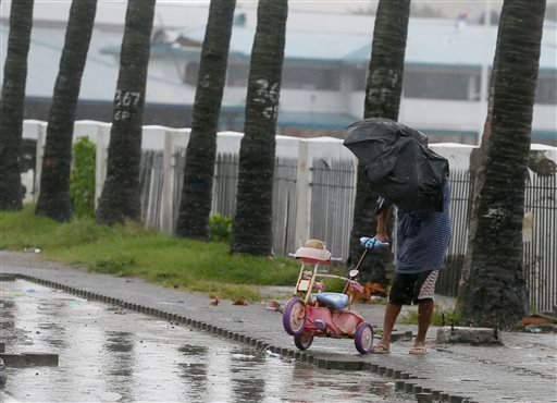 A man retrieves a baby tricycle under strong winds and slight rain brought by Typhoon Koppu Sunday, Oct. 18, 2015 in Manila, Philippines. The slow-moving typhoon blew ashore with fierce wind in the northeastern Philippines early Sunday, toppling trees and