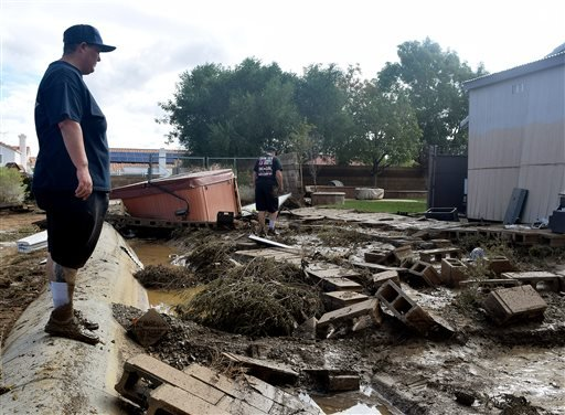 This Friday, Oct. 16, 2015 photo Rochelle Price, left, and Jen Dunnagan, who were rescued from their rooftop by firefighters after floodwater surrounded their home on Thursday, in Lancaster, Calif. The worst of the thunderstorms had passed, but the contin