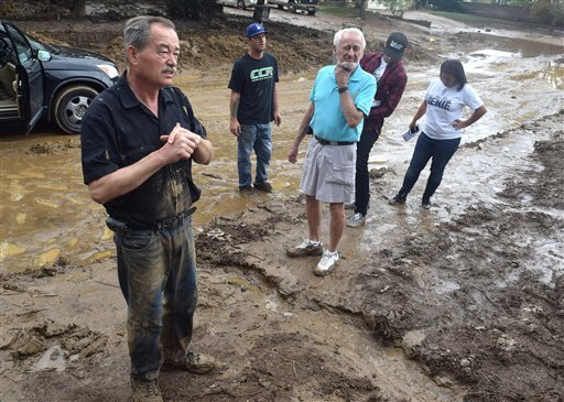 This Friday, Oct. 16, 2015 photo Brandon Clifford, left, and neighbors along Woodstone Lane in Lancaster, Calif. take in the damage to their homes after four feet of water and mud entered their homes on Thursday. The worst of the thunderstorms had passed,