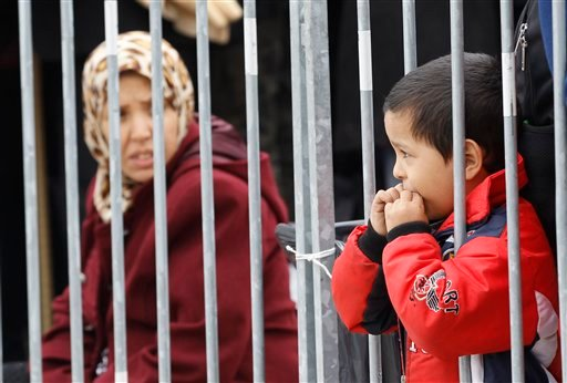 Young boy looks through bars as group of migrants waits to be registered after they arrive from Croatia in Sredisce ob Dravi, Slovenia, Sunday, Oct. 18, 2015. Hungary shut down its border with Croatia to the free flow of migrants, prompting Croatia to red