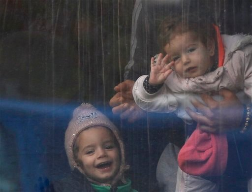 Young kids look out of a train window after they arrive from Croatia in Sredisce ob Dravi, Slovenia, Sunday, Oct. 18, 2015. Hungary shut down its border with Croatia to the free flow of migrants, prompting Croatia to redirect thousands of people toward it