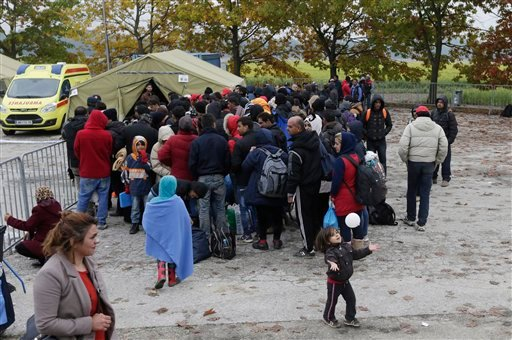 Dozens of migrants wait to be registered after arriving from Croatia in Sredisce ob Dravi, Slovenia, Sunday, Oct. 18, 2015. Hungary shut down its border with Croatia to the free flow of migrants, prompting Croatia to redirect thousands of people toward it