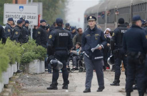 Police officers organize groups of migrants after they arrive from Croatia in Sredisce ob Dravi, Slovenia, Sunday, Oct. 18, 2015. Hungary shut down its border with Croatia to the free flow of migrants, prompting Croatia to redirect thousands of people tow