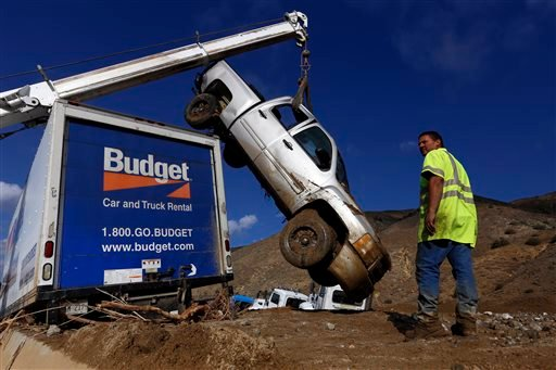 Bill Beaury, with Golden Empire Towing, works to remove vehicles on California 58 east of Tehachapi, Calif., on Saturday, Oct. 17, 2015. (Francine Orr /Los Angeles Times via AP)