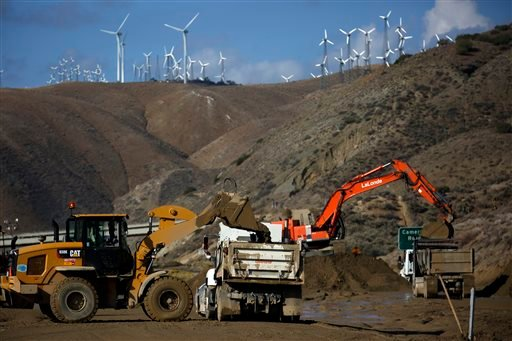 Workers remove mud and debris on California 58 east of Tehachapi, Calif., Saturday, Oct. 17, 2015. (Francine Orr /Los Angeles Times via AP)