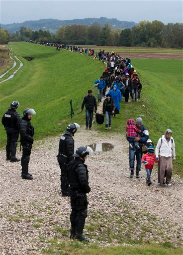 Migrants walk past Slovenian police after crossing from Croatia, in Brezice, Slovenia Monday, Oct. 19, 2015. Croatia's interior minister has rejected Slovenia's accusations that Croatia broke an agreement on limiting the numbers crossing their border to 2