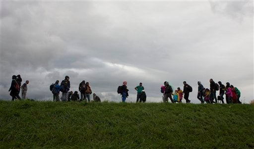 Migrants walk on a dyke after crossing from Croatia, in Brezice, Slovenia Monday, Oct. 19, 2015. Croatia's interior minister has rejected Slovenia's accusations that Croatia broke an agreement on limiting the numbers crossing their border to 2,500 a day,