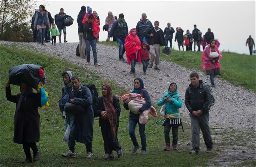 Migrants walk after crossing from Croatia, in Brezice, Slovenia Monday, Oct. 19, 2015. Croatia's interior minister has rejected Slovenia's accusations that Croatia broke an agreement on limiting the numbers crossing their border to 2,500 a day, saying the